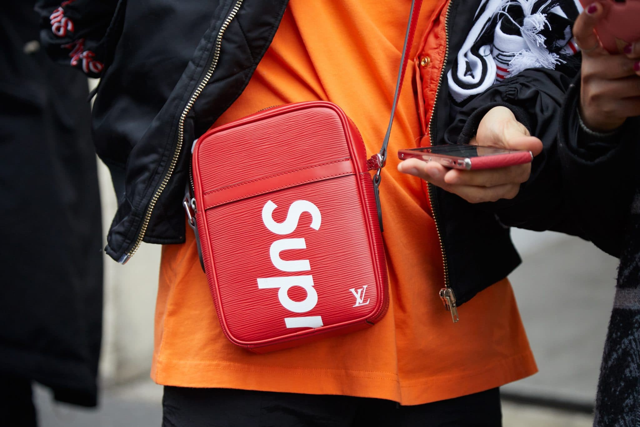 MILAN - JANUARY 15: Man with orange shirt and red Louis Vuitton Supreme bag looking at phone before Represent fashion show, Milan Fashion Week street style on January 15, 2018 in Milan.